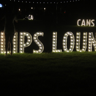Clips Lounge sign with cans sign in background